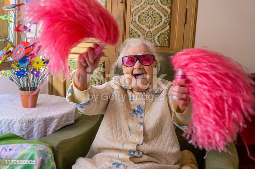 Cheerleader pom-pom elderly woman happy at living room