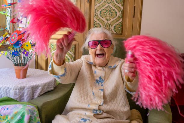 cheerleader pom-pom oudere vrouw gelukkig - pompon stockfoto's en -beelden