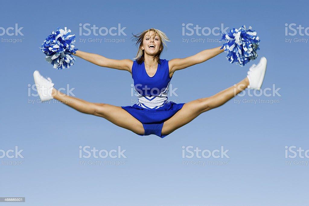 Cheerleader With Pompoms Doing Splits Against Sky stock photo