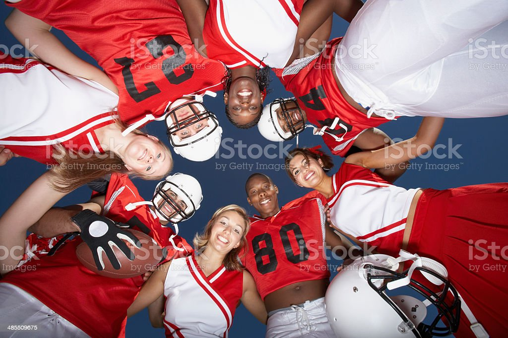 Cheerleaders and Football Players in Huddle stock photo