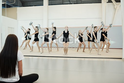 Group of energetic teenage cheerleaders with pompoms dancing at dress rehearsal in front of coach