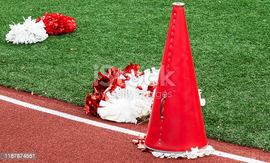 A red megaphone used by cheerleaders on the track next to red and white pom poms on the green turf.
