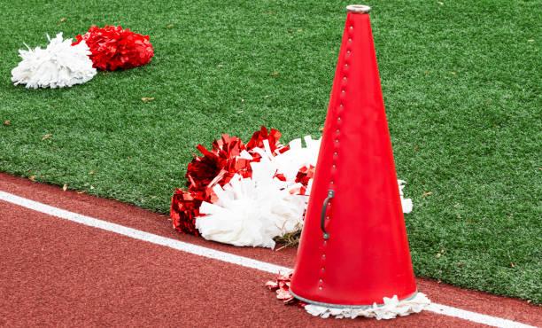 cheerleaders megafoon en pom poms - pompon stockfoto's en -beelden