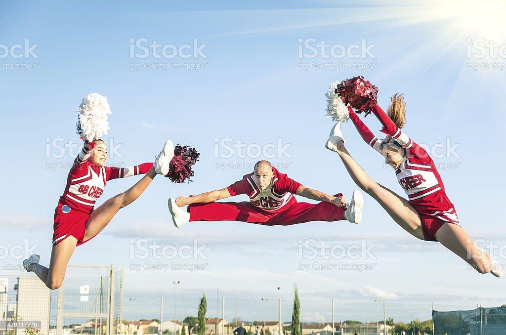 Cheerleader team, ein Sprung mit männlich-Coach – Foto