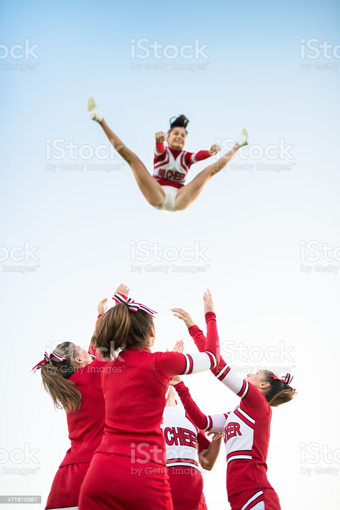 Cheerleaders throw up a girl in the air royalty-free stock photo