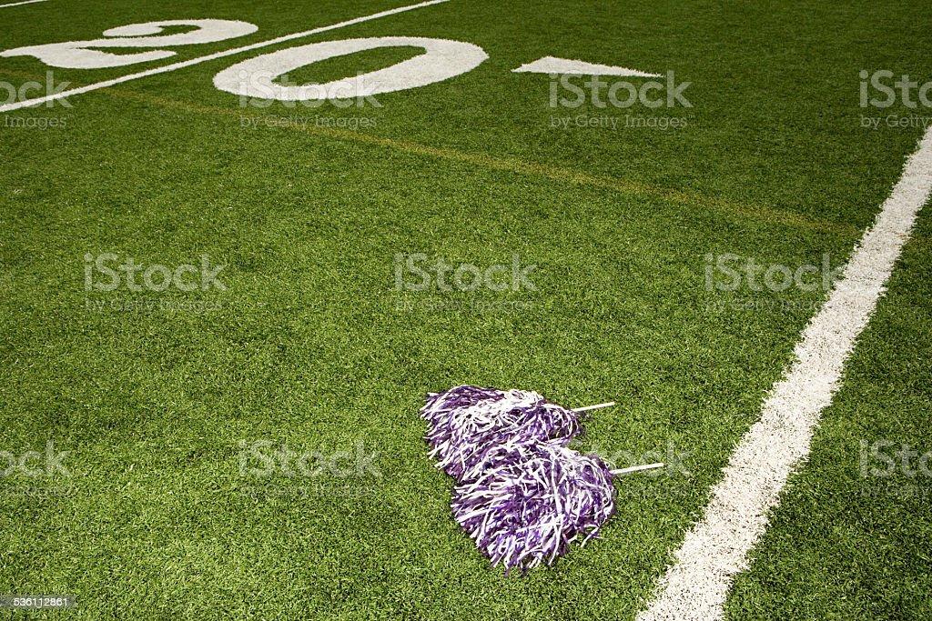 Cheerleading pom-poms on football field stock photo