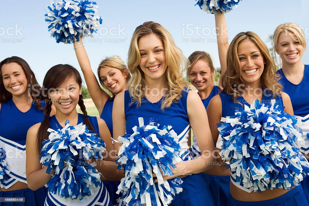 Cheerleading squad dressed in blue and white pose for photo stock photo
