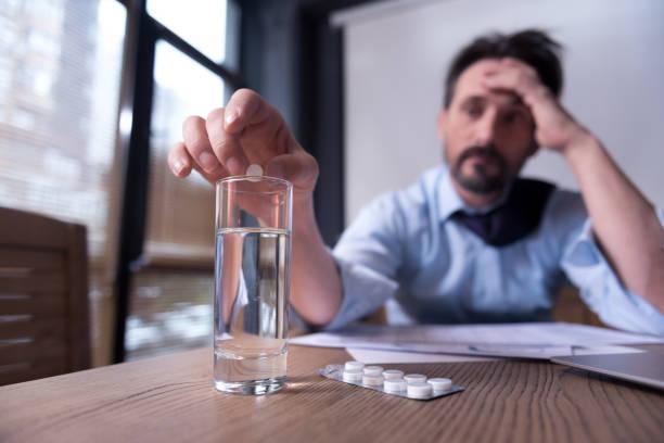 cheerless depressed man taking medicine - leitungswasser trinken stock-fotos und bilder