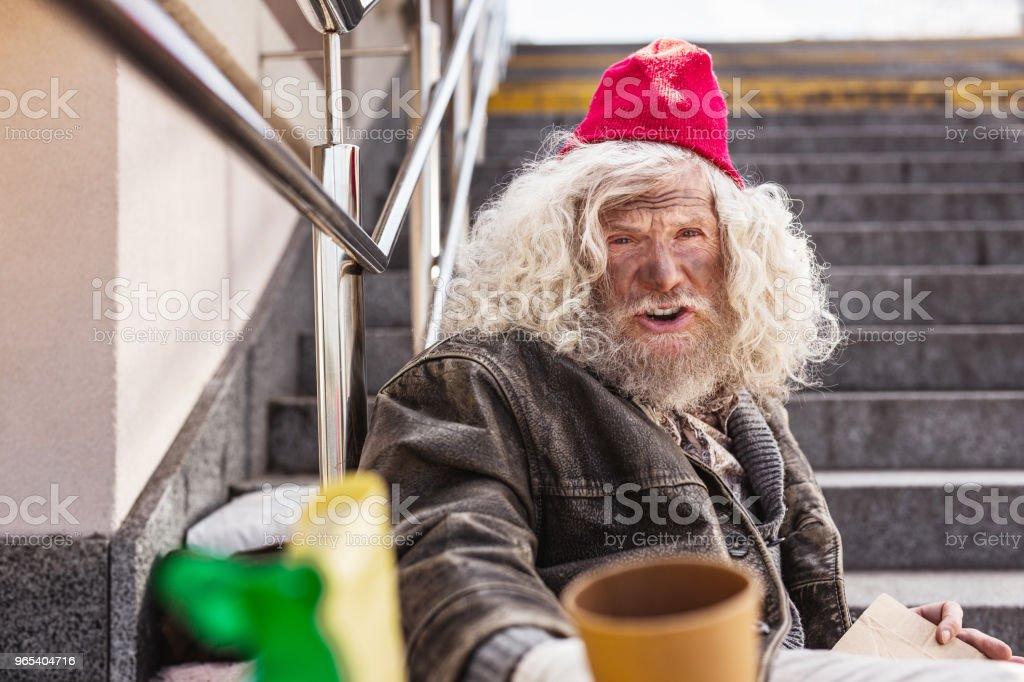 Cheerless homeless man sitting on the street royalty-free stock photo