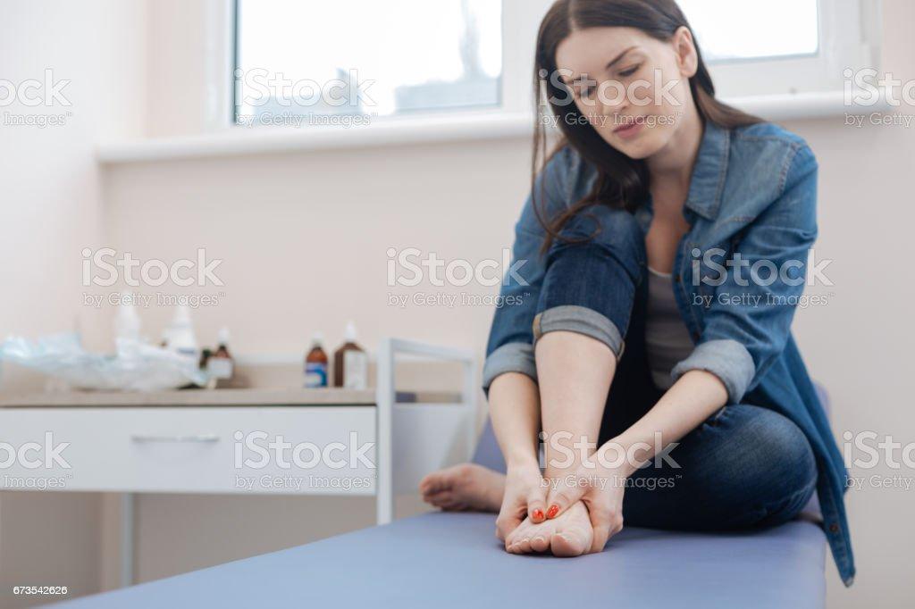 Cheerless moody woman holding her feet stock photo