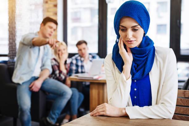 fröhliche muslimische frau fühlt sich von der gesellschaft ungerecht - vorurteil stock-fotos und bilder