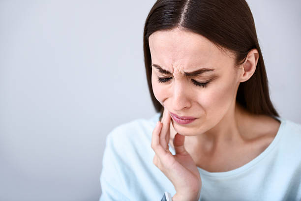 Cheerless woman having toothache stock photo