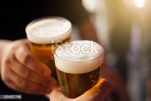 istock Cheers! Clink glasses. Close-up shots of hands holding beer glasses and beer bubbles. 1204327755