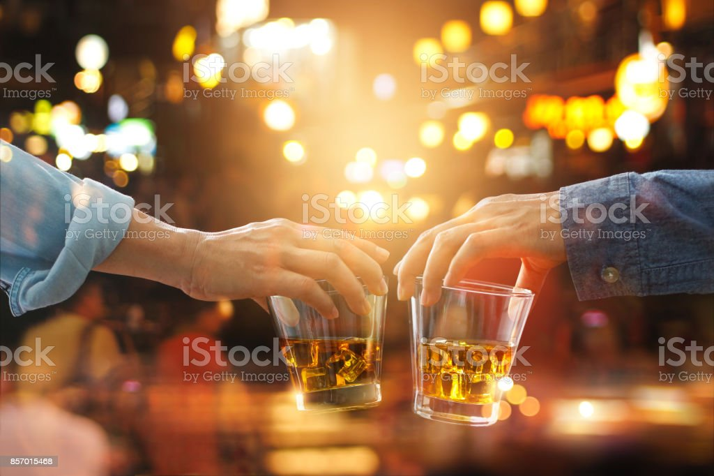 Cheers clinking of friends with bourbon whisky drink in party night after work on colorful background stock photo