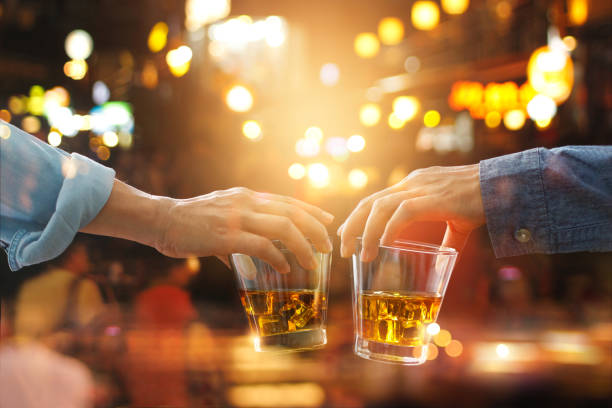 cheers clinking of friends with bourbon whisky drink in party night after work on colorful background - whiskey stock photos and pictures