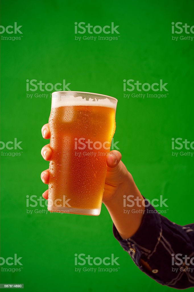 Cheers   Ice cold beer    Hand with beer glass making toast stock photo