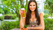 Young woman wearing a dirndl, holding a pretzel and drinking some beer - ready for Munich's Oktoberfest!