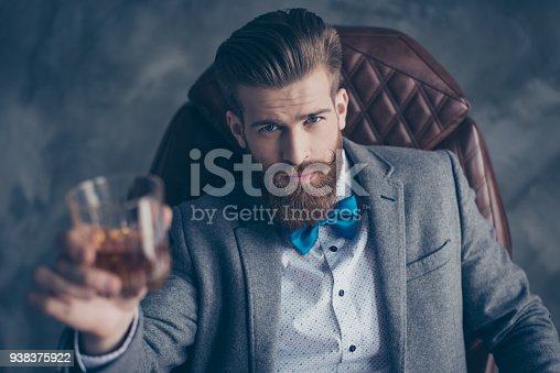 istock Cheers, ladies and gentlemen! Stylish elegant red bearded aristocrat in suit and bowtie holds glass with brandy, relaxing, sits on leather brown arm chair indoors 938375922