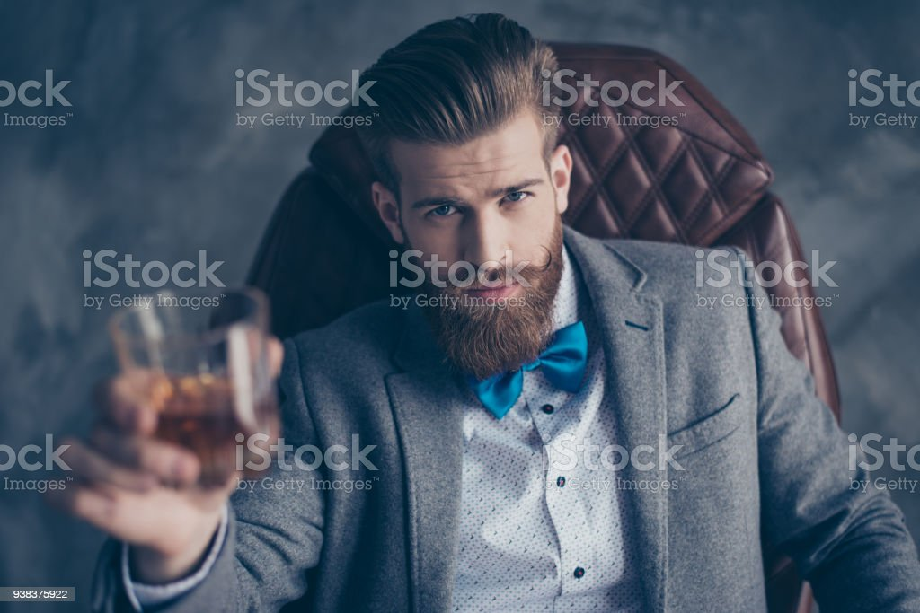 Cheers, ladies and gentlemen! Stylish elegant red bearded aristocrat in suit and bowtie holds glass with brandy, relaxing, sits on leather brown arm chair indoors stock photo