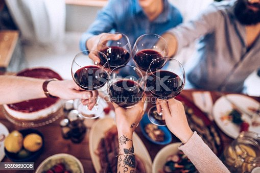 Five people drinking wine after dinner
