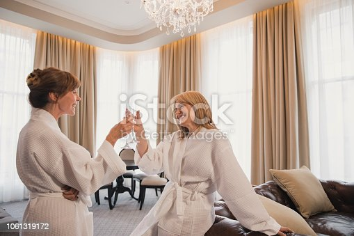 Two mature women are making a toast in their hotel room with champagne.