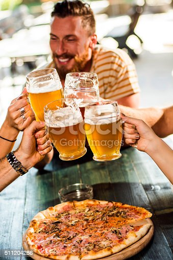 Group of friends making a toast in the pub