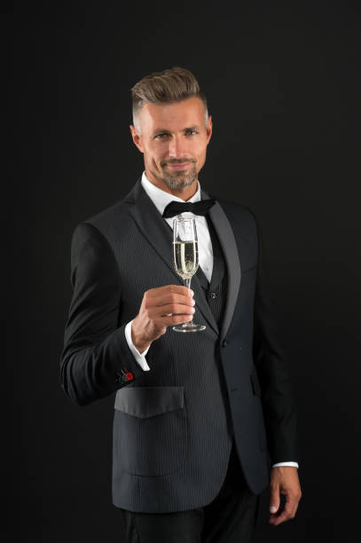 Cheers. Sincere greetings. Appreciate classics. Bearded man with formal look. Hipster black background. Brutal man in tuxedo suit. Classic can make man look smarter. Celebrate with champagne glass stock photo