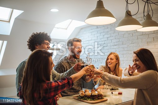 Group of friends having a toast and a good time while eating junk food and drinking beer.