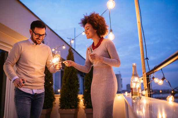 Cheers to us Photo of a young couple celebrating with sparklers on the terrace. date night romance stock pictures, royalty-free photos & images