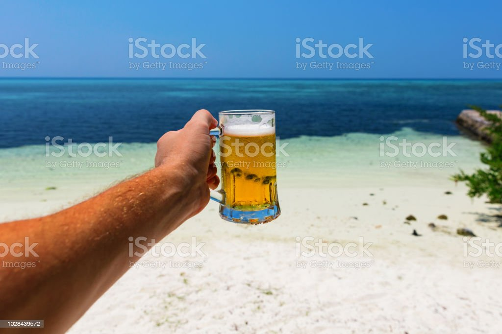 Cheers with a beer from a tropical beach stock photo