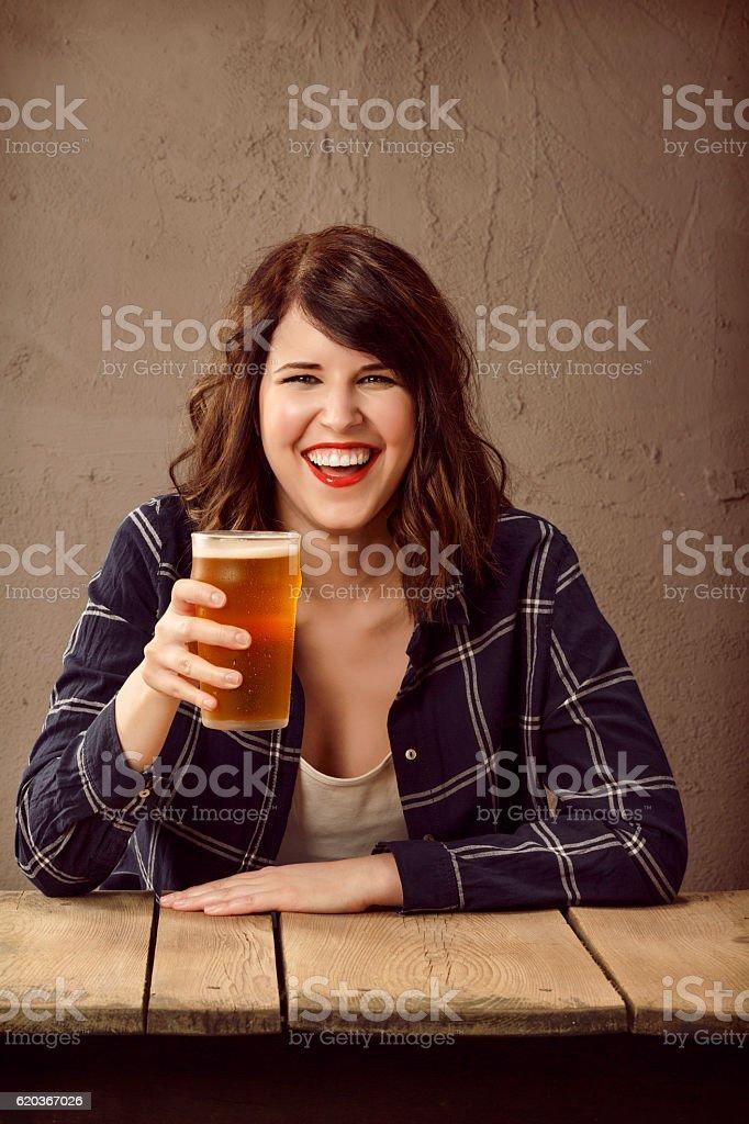 Pozdrowienia Młoda kobieta siedzi w barze i picie piwa zbiór zdjęć royalty-free