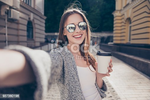 istock Cheert! Selfie time! Young happy lady in a spring vacation, walking in the city, drinking coffee, photographing herself on a sunny day 937380198