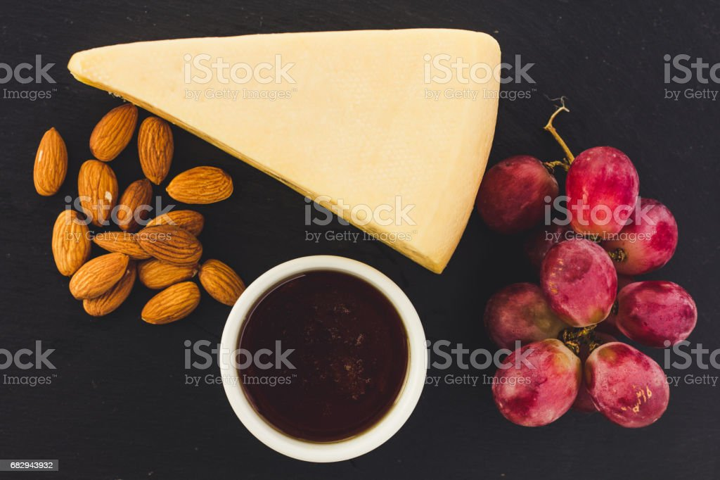 Cheese, almond, grapes and honey on black plate royalty-free stock photo