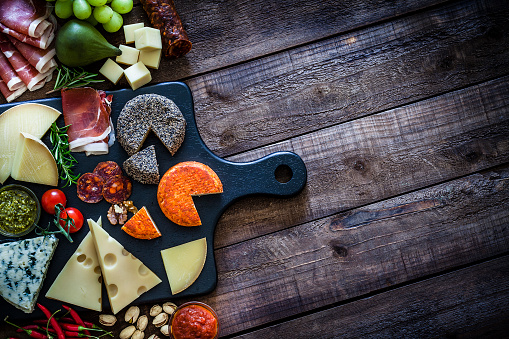 istock Cheese and cold meat board shot from above on wooden table 975737074