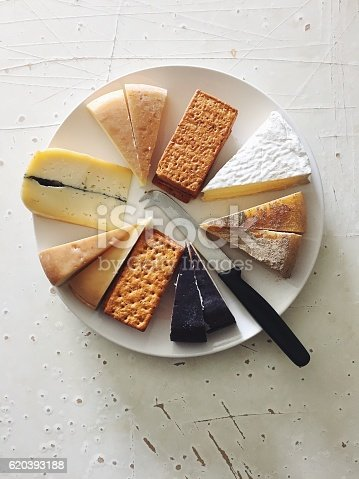 istock Cheese and cracker plate with knife on rustic white background 620393188