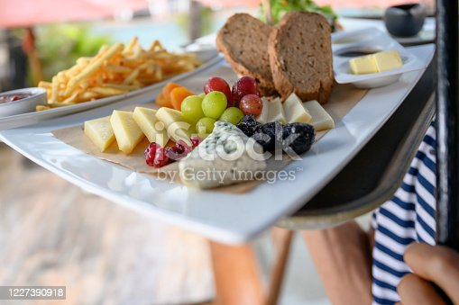 Unrecognizable wait staff carrying serving tray with cheese and fruit, Nikon Z7
