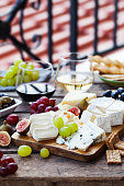 istock Cheese and fruits assortment on cutting board with red and white wine on wooden background. Copy space. 1178069984
