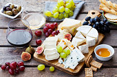 istock Cheese and fruits assortment on cutting board with red, white wine on wooden background. 1177028889