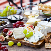 istock Cheese and fruits assortment on cutting board with red, white wine on wooden background. Copy space. 1177028934