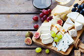 istock Cheese and fruits assortment on cutting board with red, white wine on wooden background. Copy space. 1177030067