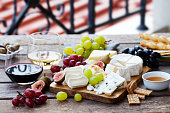 istock Cheese and fruits assortment on cutting board with red, white wine on wooden background. Copy space. 1178066815