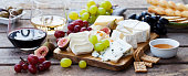 istock Cheese and fruits assortment on cutting board with red, white wine on wooden background. 1178919272