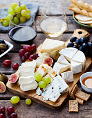 istock Cheese and fruits on cutting board with red, white wine on wooden background. 1182825223