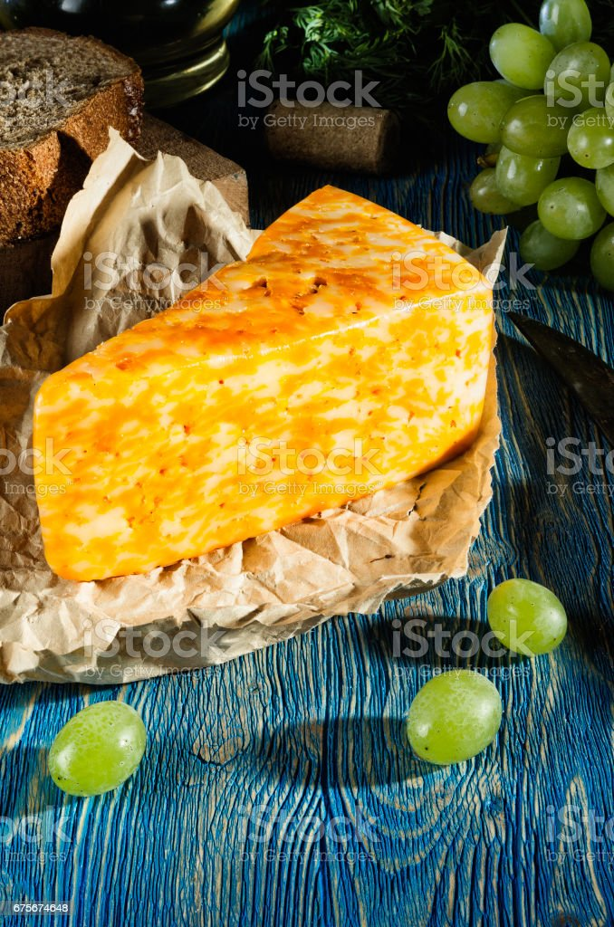 Cheese and grapes lying on a wooden table royalty-free stock photo