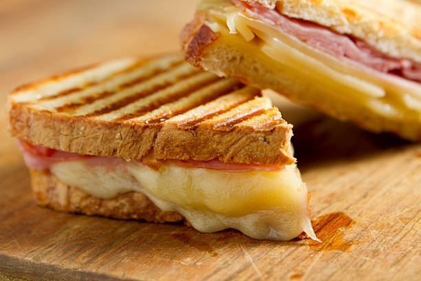 cheese and ham panini sandwiches on a wooden board - cheese sandwich bildbanksfoton och bilder
