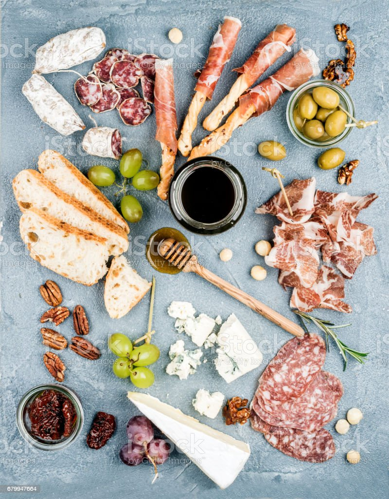 Cheese and meat appetizer selection or wine snack set. Variety of  cheese, salami, prosciutto, bread sticks, baguette, honey, grapes, olives, sun-dried tomatoes, pecan nuts over grey concrete textured backdrop, top vie stock photo
