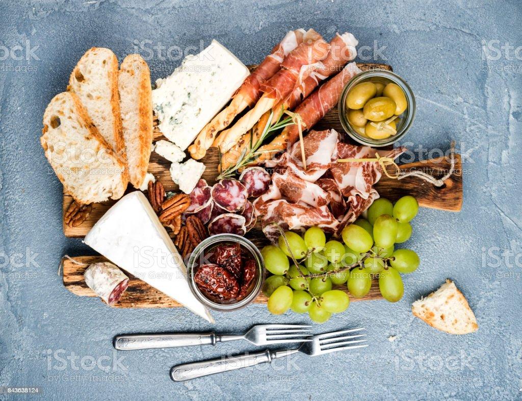 Käse und Fleisch Vorspeise Auswahl oder Wein Snack festgelegt. Vielzahl von Salami, Schinken, Brot-Sticks, Baguette, Honig, Trauben, Oliven, getrocknete Tomaten, vie Pekannüsse über grauen Beton strukturierte Kulisse, top – Foto
