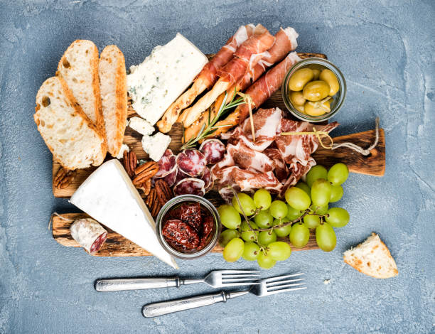 Cheese and meat appetizer selection or wine snack set. Variety of  , salami, prosciutto, bread sticks, baguette, honey, grapes, olives, sun-dried tomatoes, pecan nuts over grey concrete textured backdrop, top vie stock photo