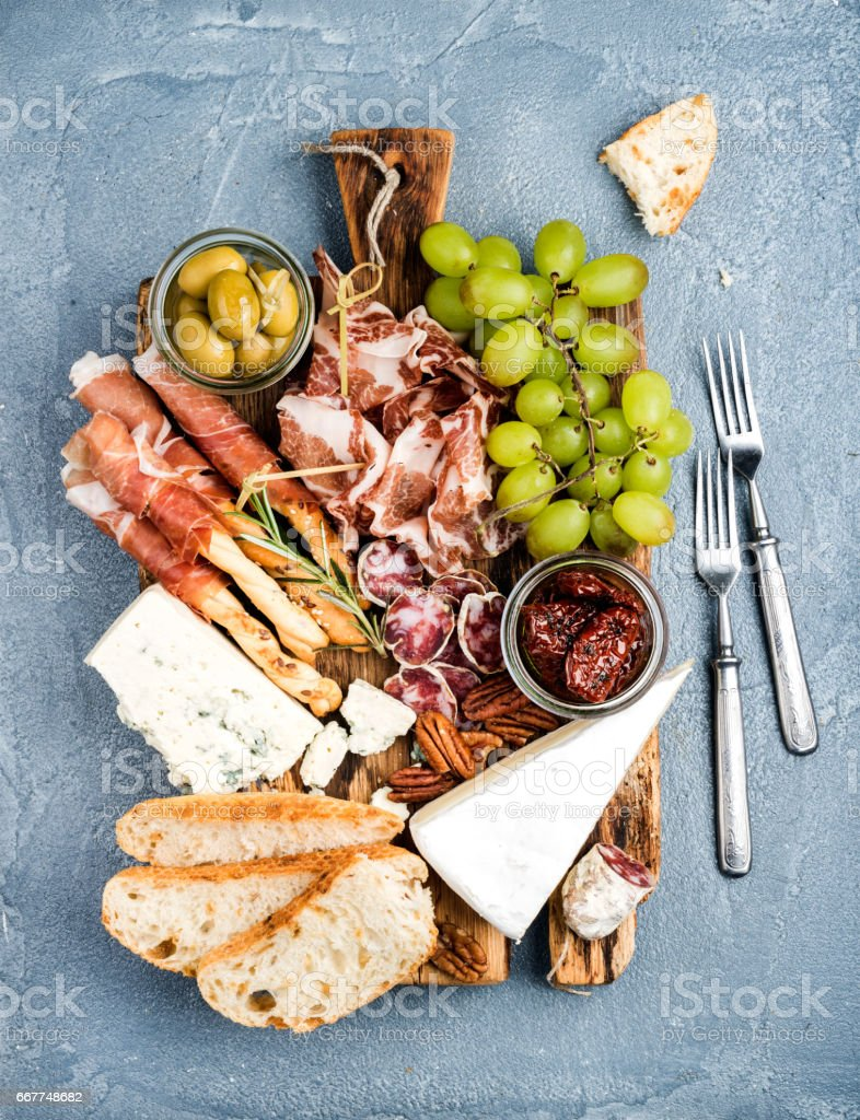 Cheese and meat appetizer selection. Prosciutto di Parma, salami, bread sticks, baguette slices, olives, sun-dried tomatoes, grapes nuts on rustic wooden board stock photo
