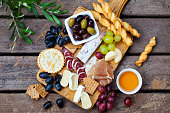 istock Cheese and meat appetizers on cutting board on wooden background. Top view. 1189178290